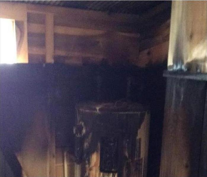 charred interior of shed and fire-destroyed water heater