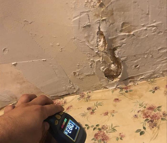 water damage on ceiling due to a broken pipe leaking, paint is cracked and bubbling, moisture meter reading wet