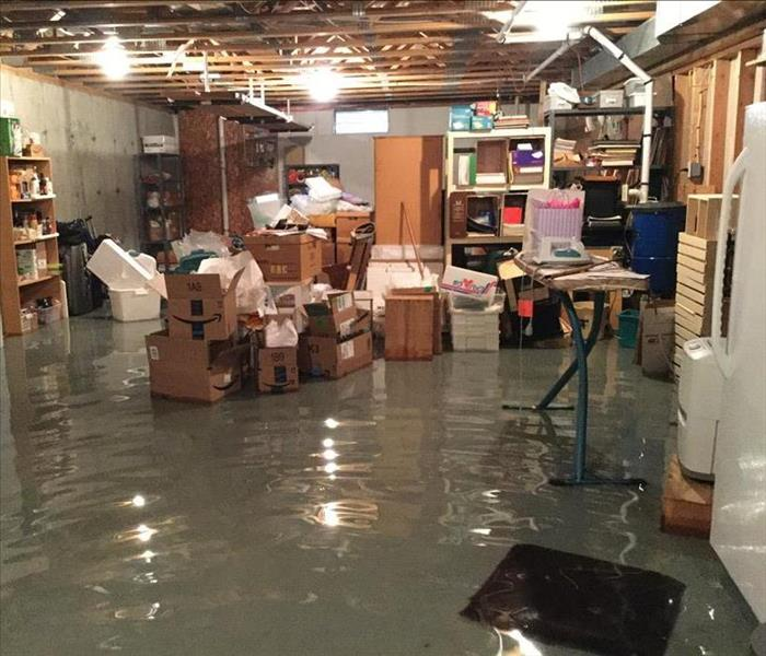 photo of inch of water in an unfinished basement with a lot of boxes and appliances