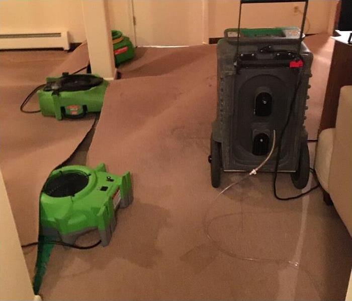 photo of air movers pointed underneath a water damaged carpet and a dehumidifer